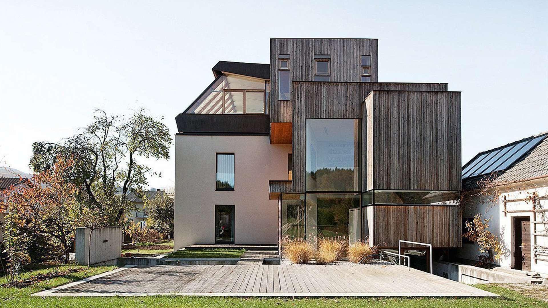 großes Wohnhaus mit Holzfenstern und Terrasse im Vordergrund