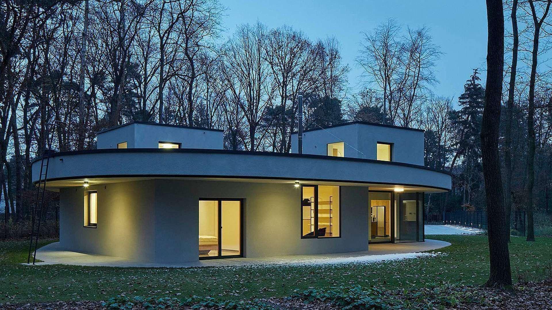 ausgefallenes rundes Haus mit Kunststoff-Aluminium-Fenstern bei Dämmerung im Wald