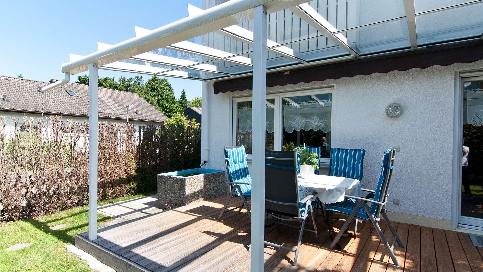 weißes Terrassendach auf einer Terrasse mit Gartenmöbeln