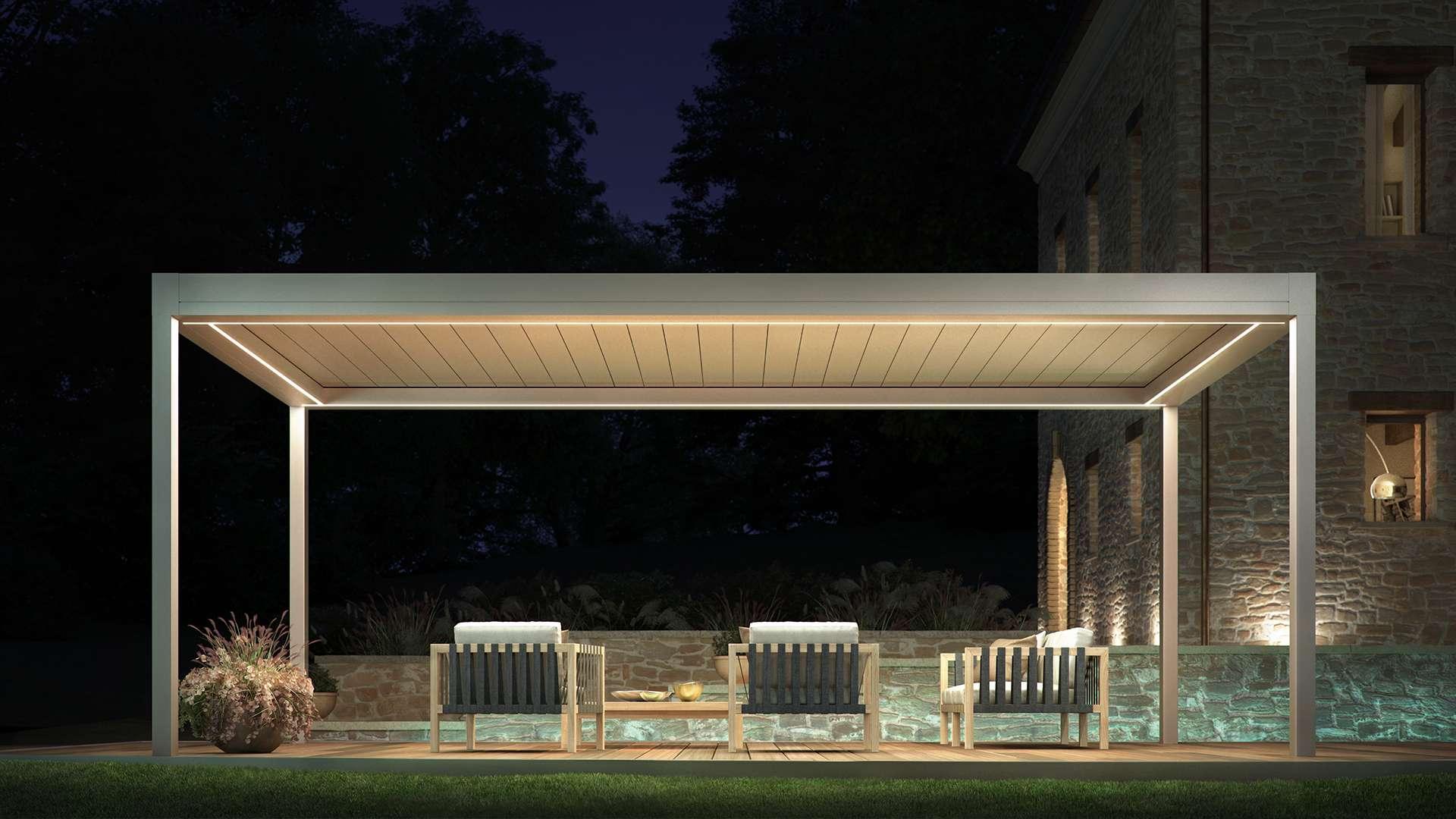Pratic Lamellendach Brera S mit zwei Liegestühlen bei Nacht
