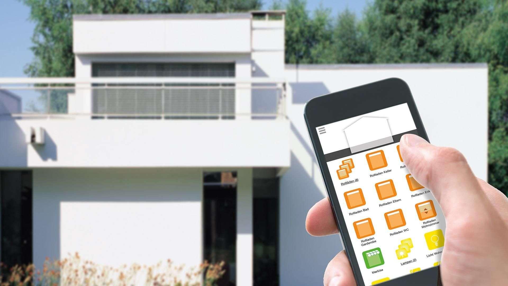 Hand mit Smart Home Steuerung vor einen Wohnhaus