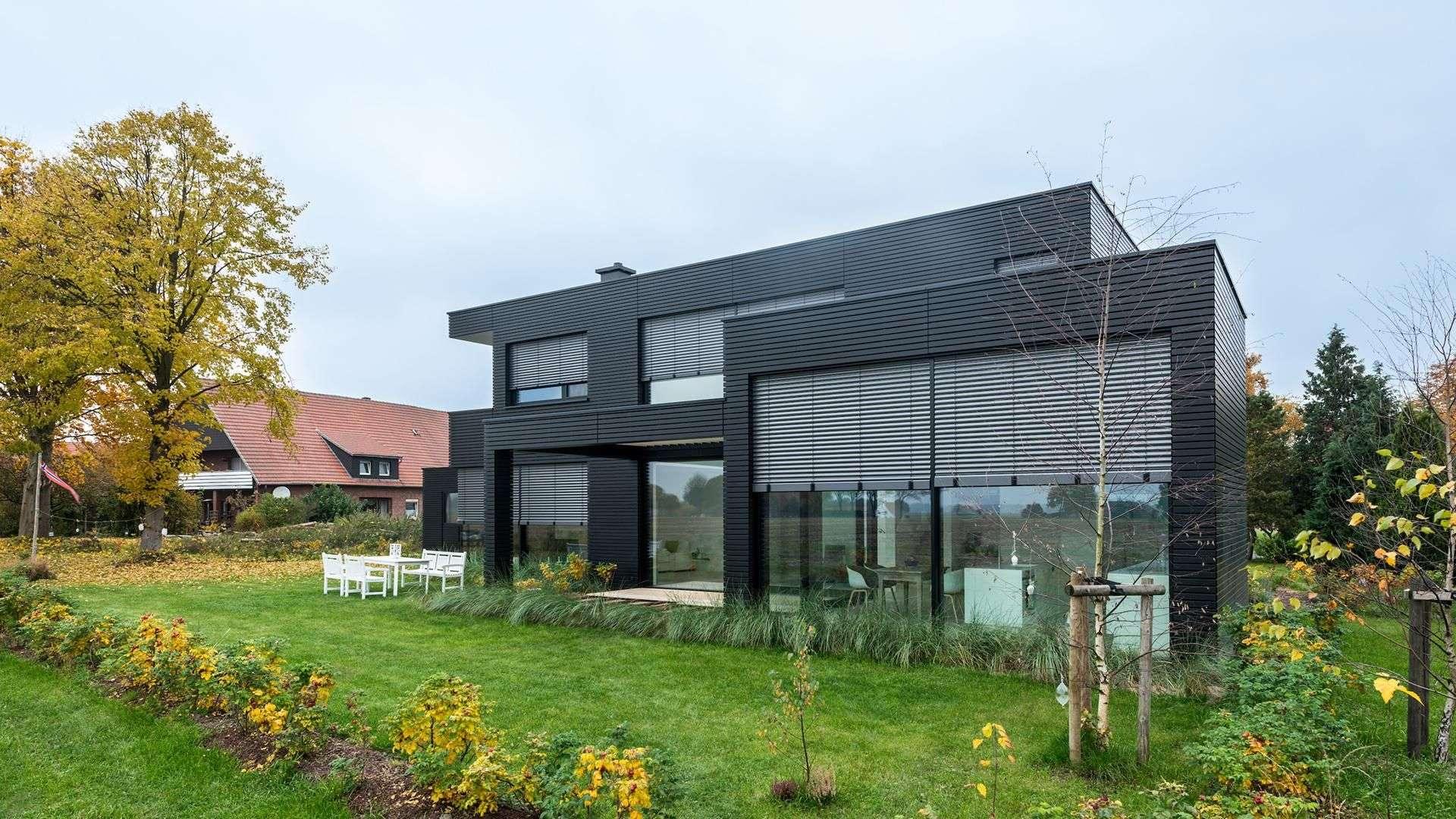 schwarzes Flachdachhaus mit Rollos zur Beschattung vor den Fenstern und großem Garten