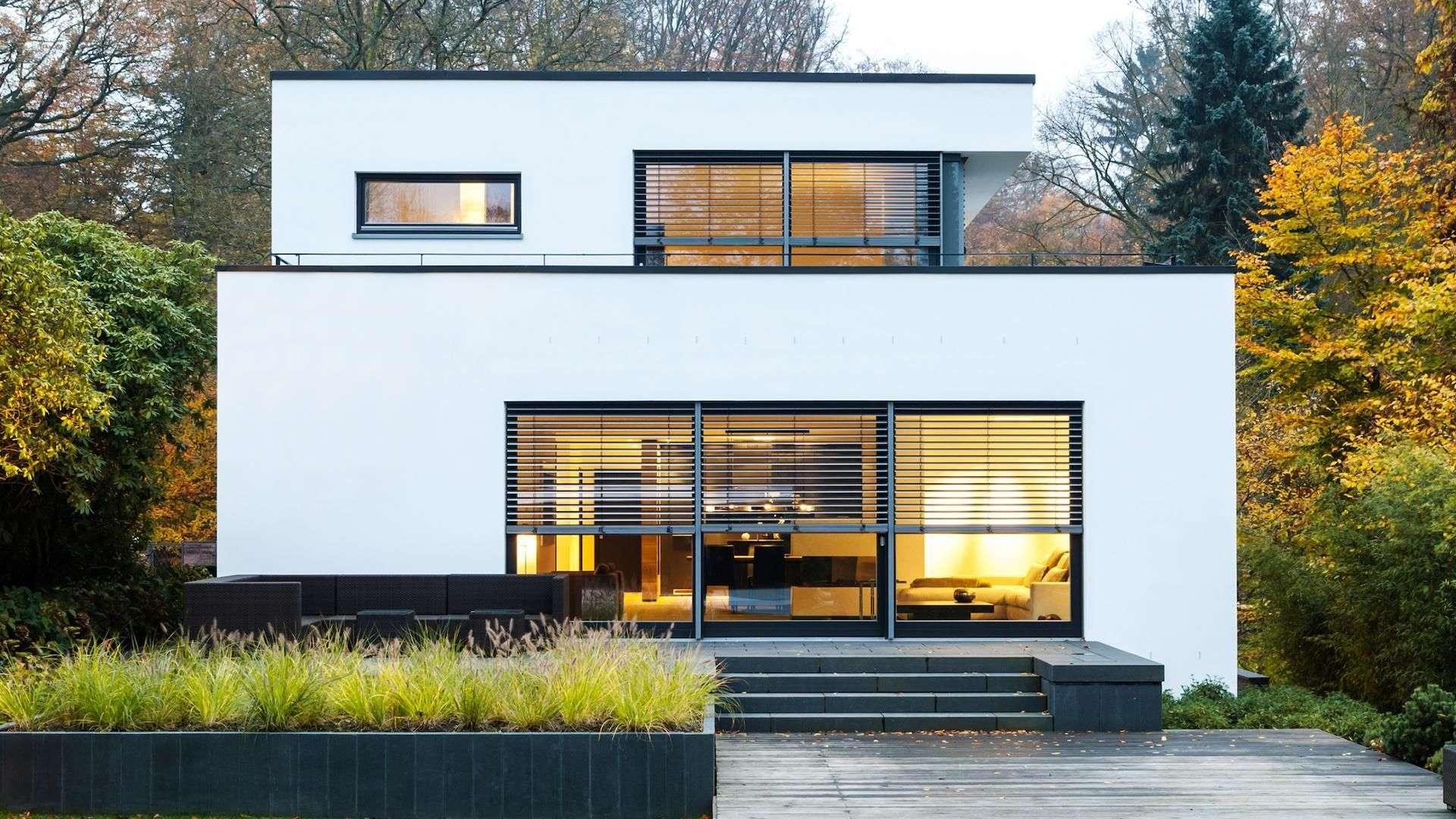 Flachdachhaus mit Wald mit Beschattungsmarkisen vor den Fenstern