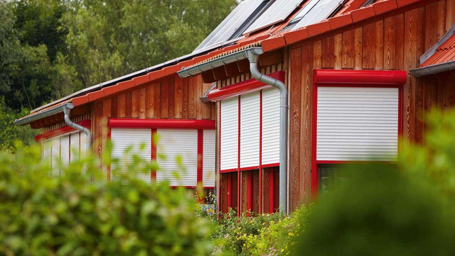 Seitenansicht auf ein Holzhaus mit Rollläden vor den Fenstern