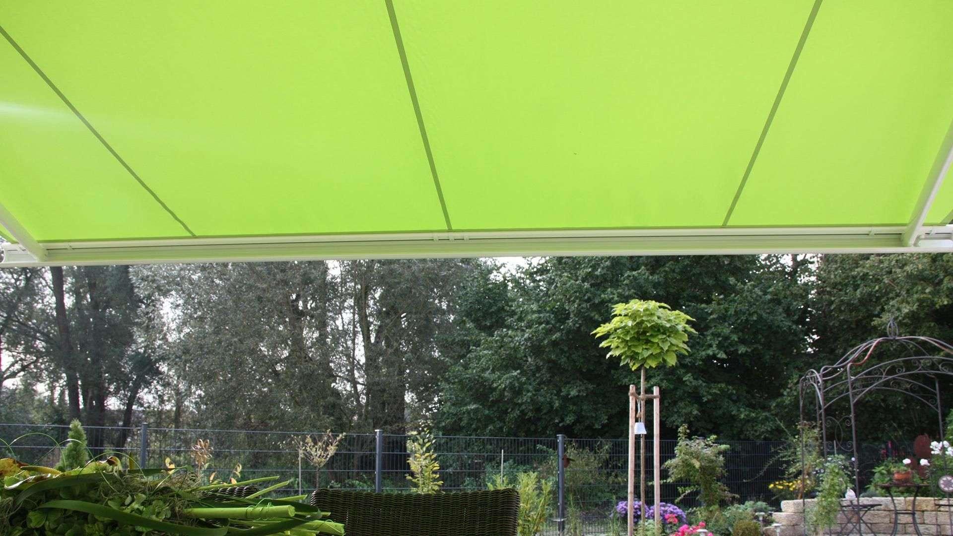 Blick unter eine hellgrüne Markise mit Blick in den Garten
