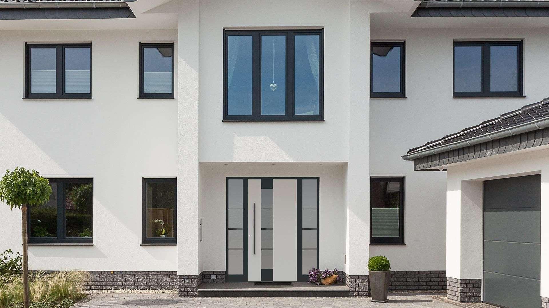 große weiße Villa mit weißer Aluhaustür und vielen Fenstern