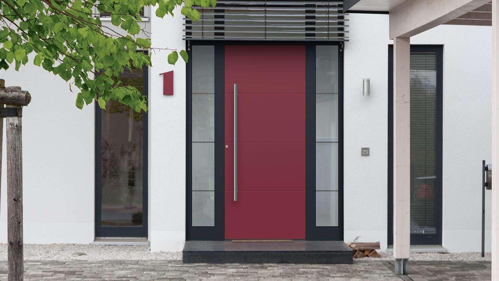 dunkelrote Aluhaustür mit Glaselementen links und rechts in weißer Fassade