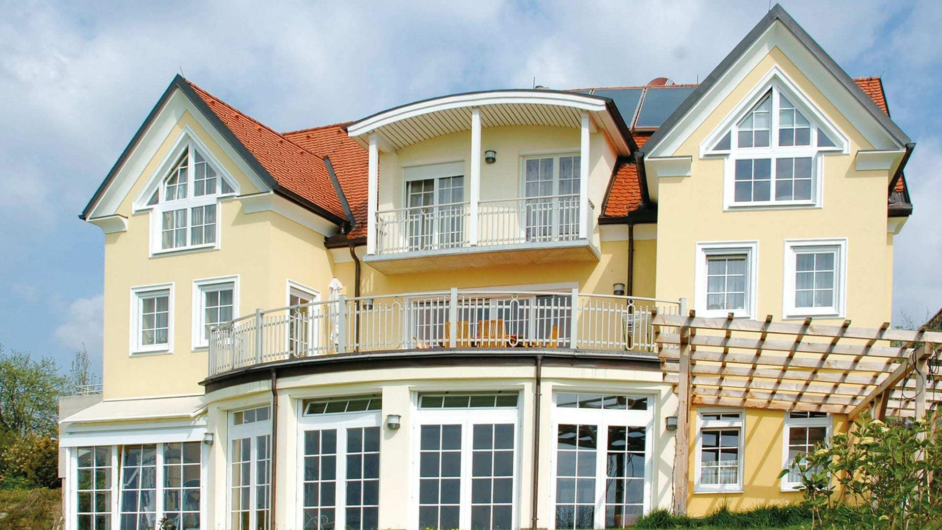 hellgelbes Haus mit vielen Fenstern und langer Fensterfront im Erdgeschoss