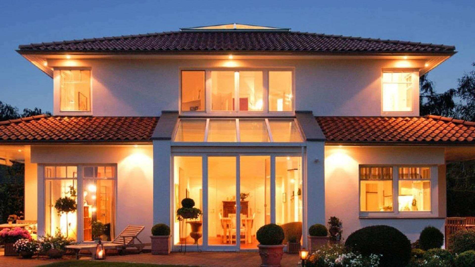 weißes Wohnhaus mit Holzfenstern und Beleuchtung bei Dämmerung