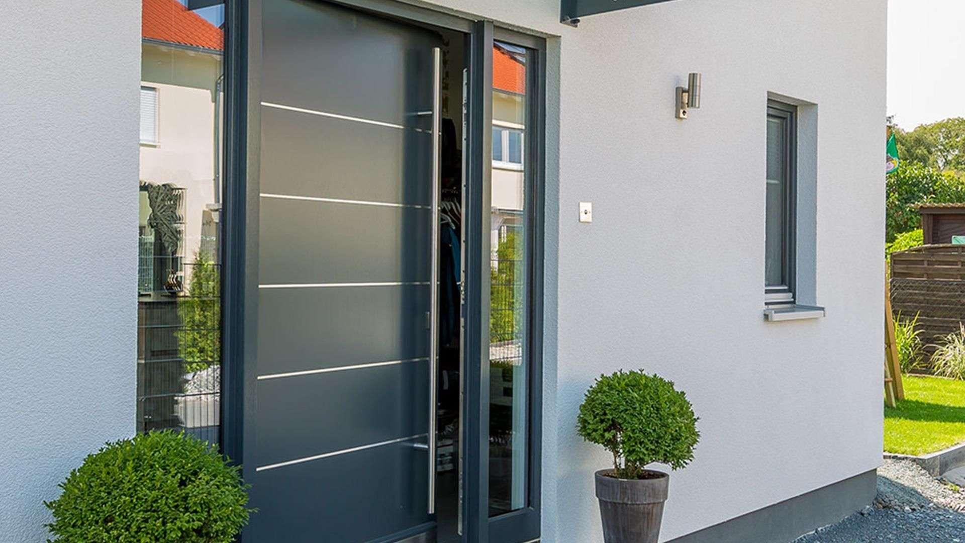 graue Holzhaustür mit Glaselemente links und rechts in einer weißen Fassade