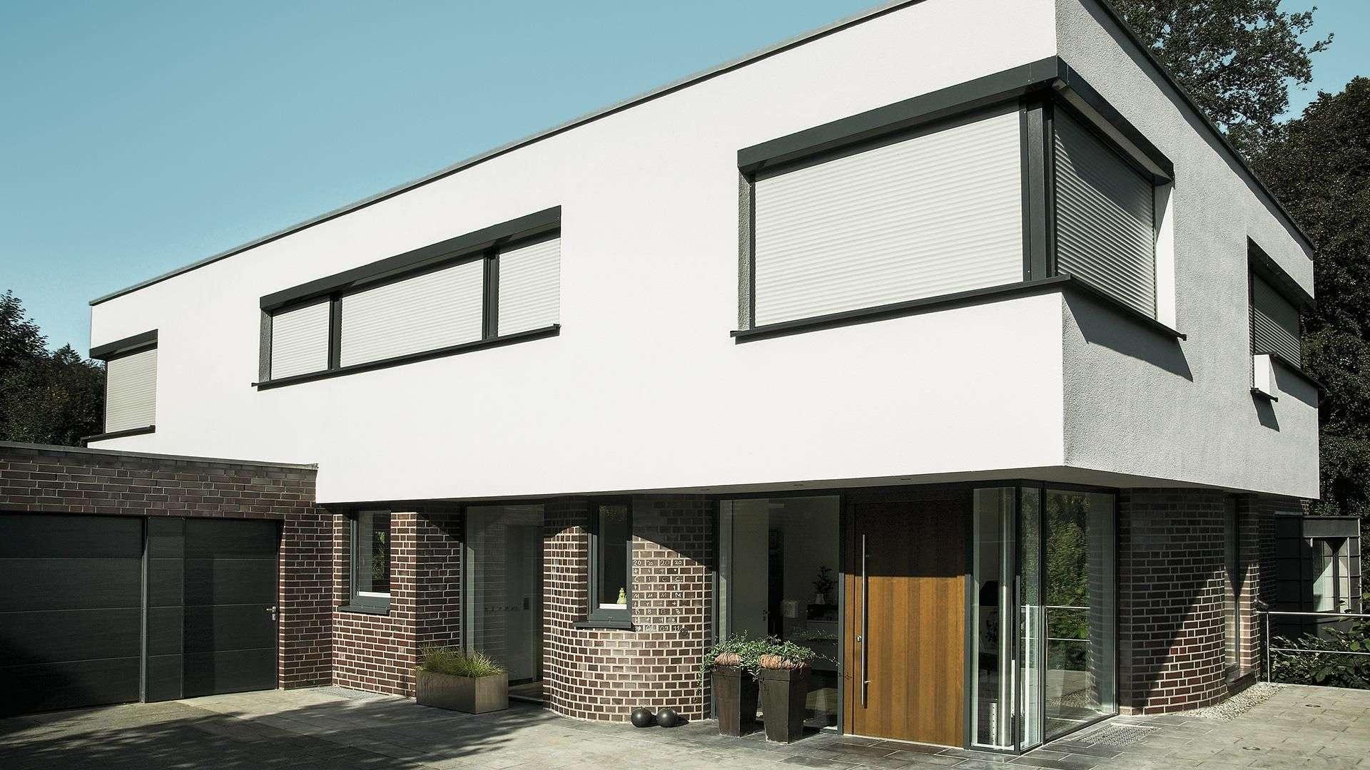 weißes Wohnhaus mit großen Fenstern mit runtergelassenen Rollläden