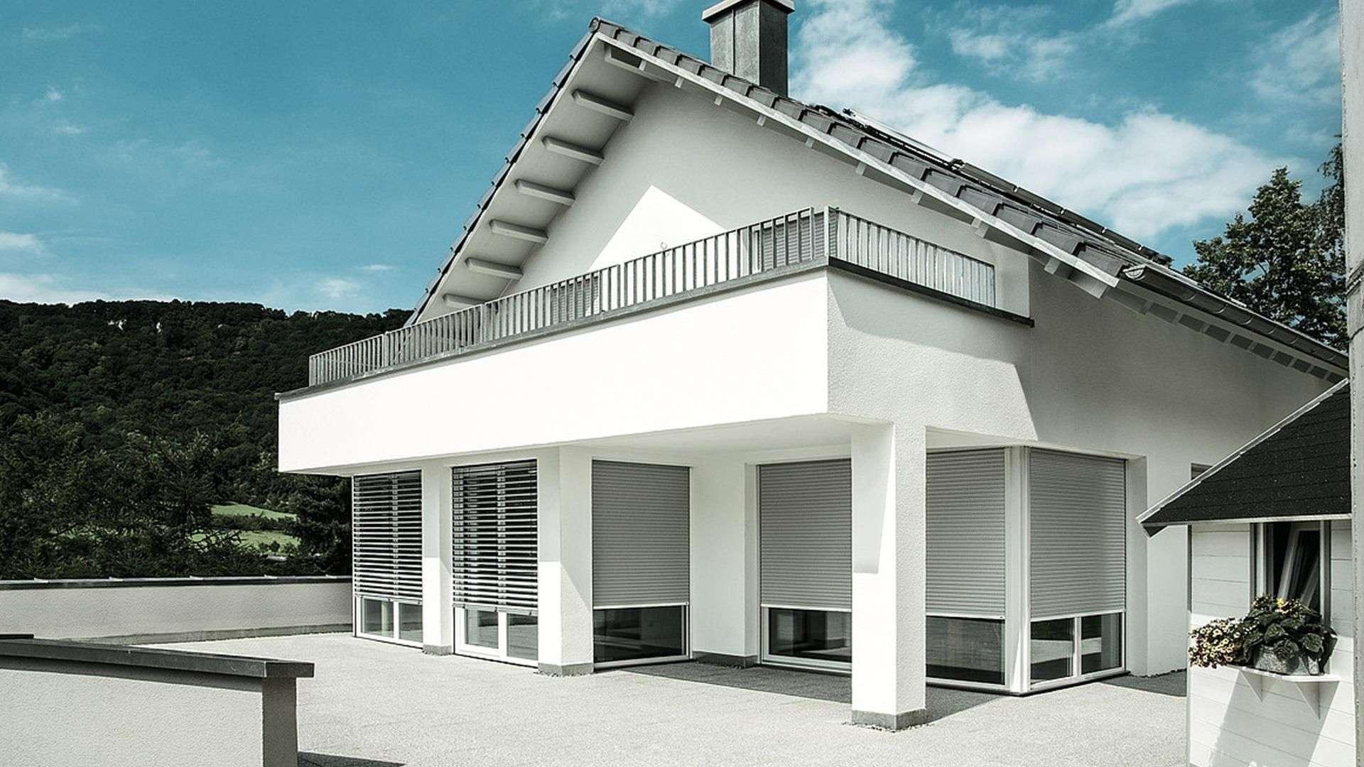 weißes Wohnhaus mit großem Balkon und Raffstoren vor den Fenstern