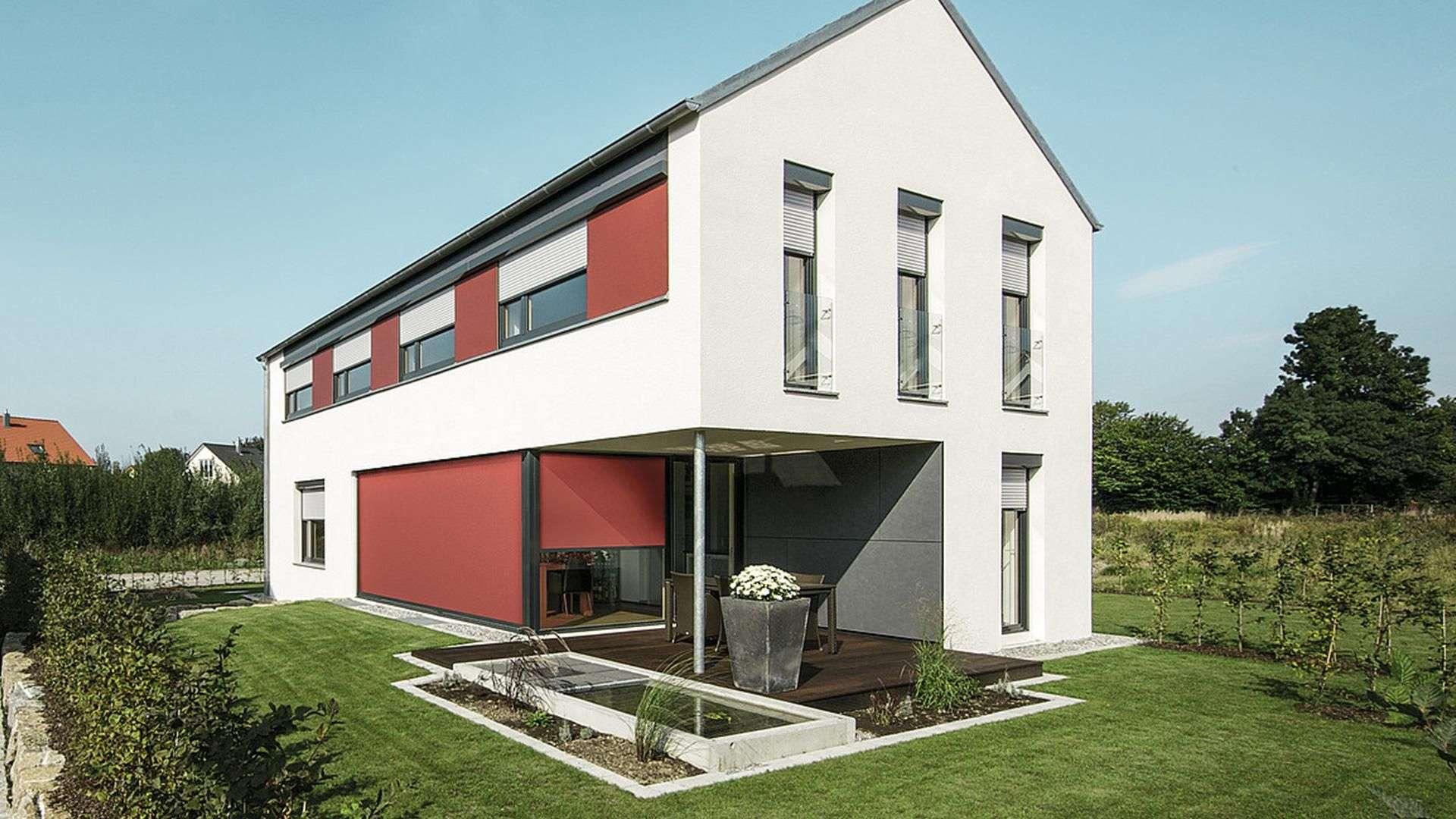 rot-weißes Wohnhaus mit großen Fenster mit Rollläden und großem Garten