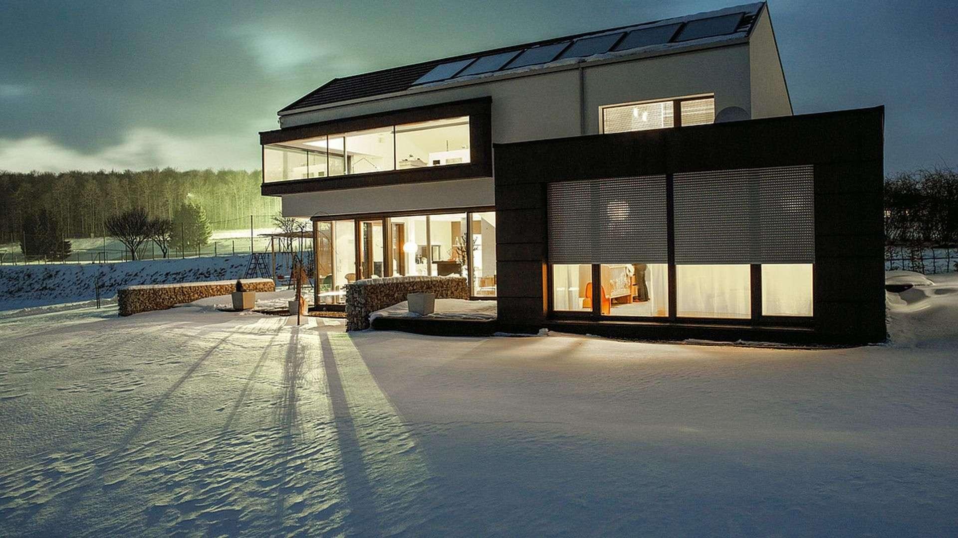 großes Wohnhaus mit vielen Fenster mit Rollläden. Drinnen ist das Haus beleuchtet, außen ist Dämmerung.