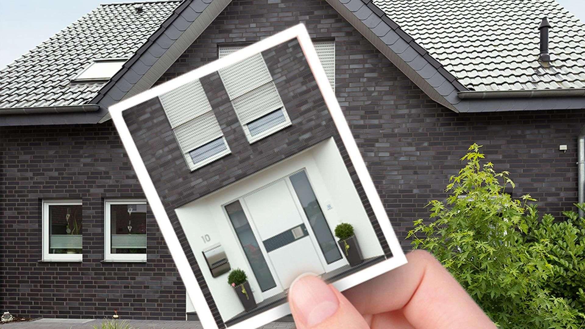 Hand hält Foto einer Haustürvisualisierung vor ein graues Wohnhaus