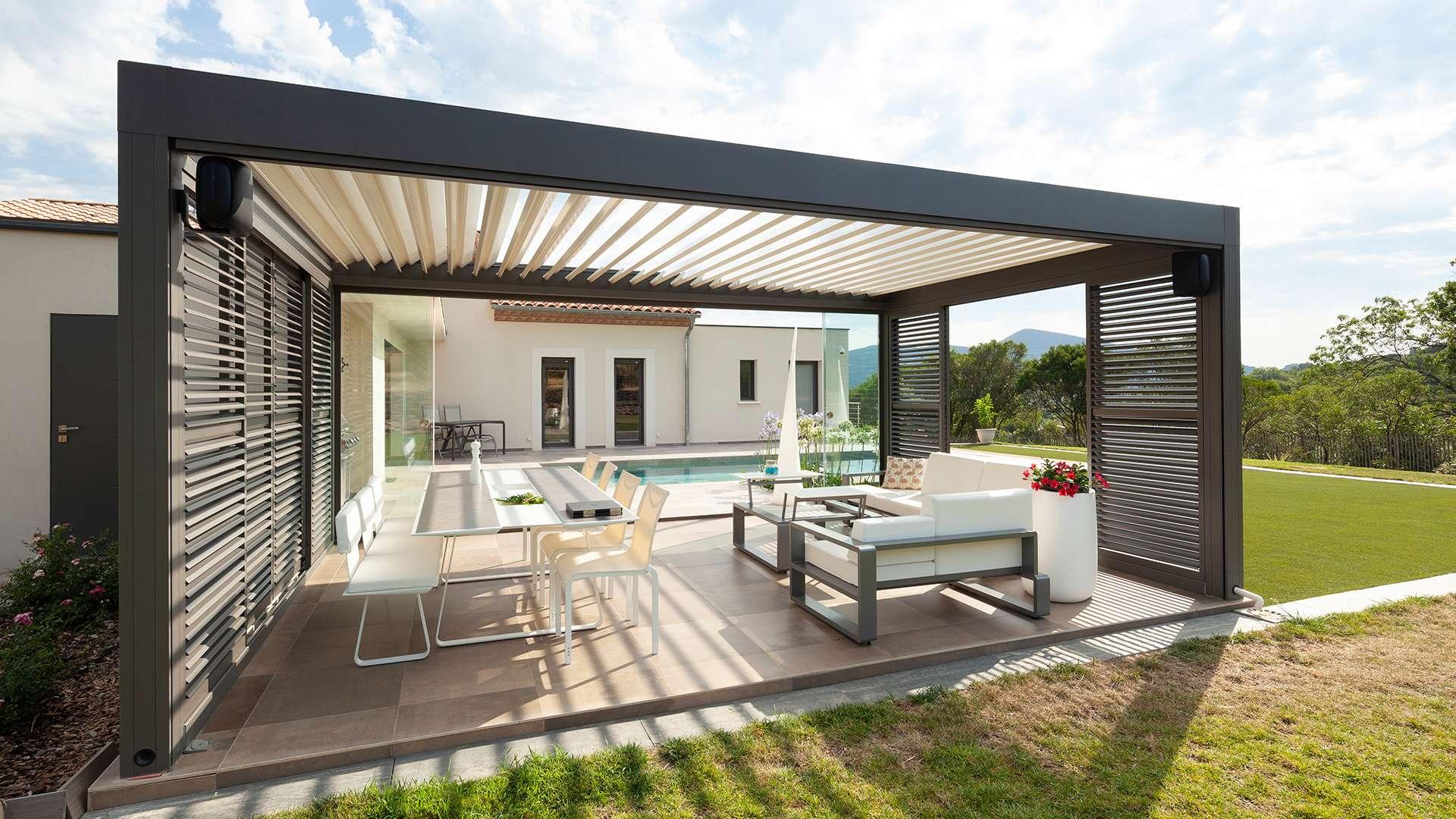 freistehendes Camargue Lamellendach mit Sitzmöbeln in einem Garten