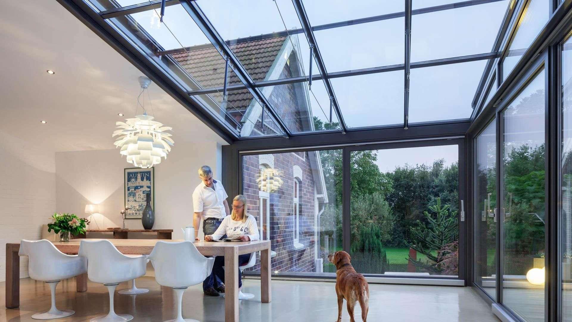 Innenanischt eines Solarlux SDL Akzent Vision Wintergartens mit Esstisch, an dem einen Frau sitzt. Mann steht hinter der Frau und im Wintergarten läuft ein Hund