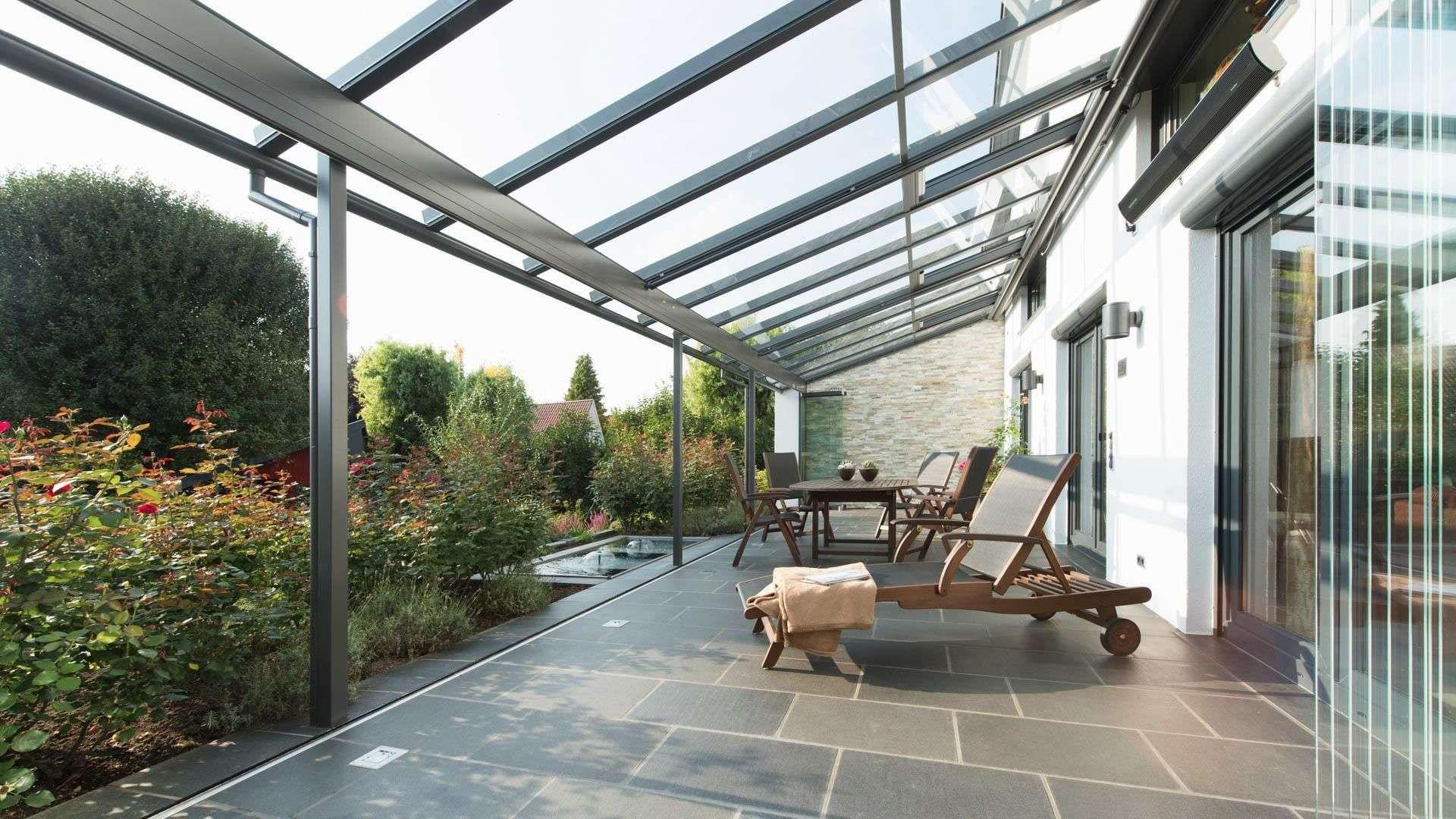 Innenansicht eines Solarlux SDL Atrium plus Terrassendaches mit geöffneter Glas-Front, Liegestuhl sowie Sitzmöbeln im Inneren