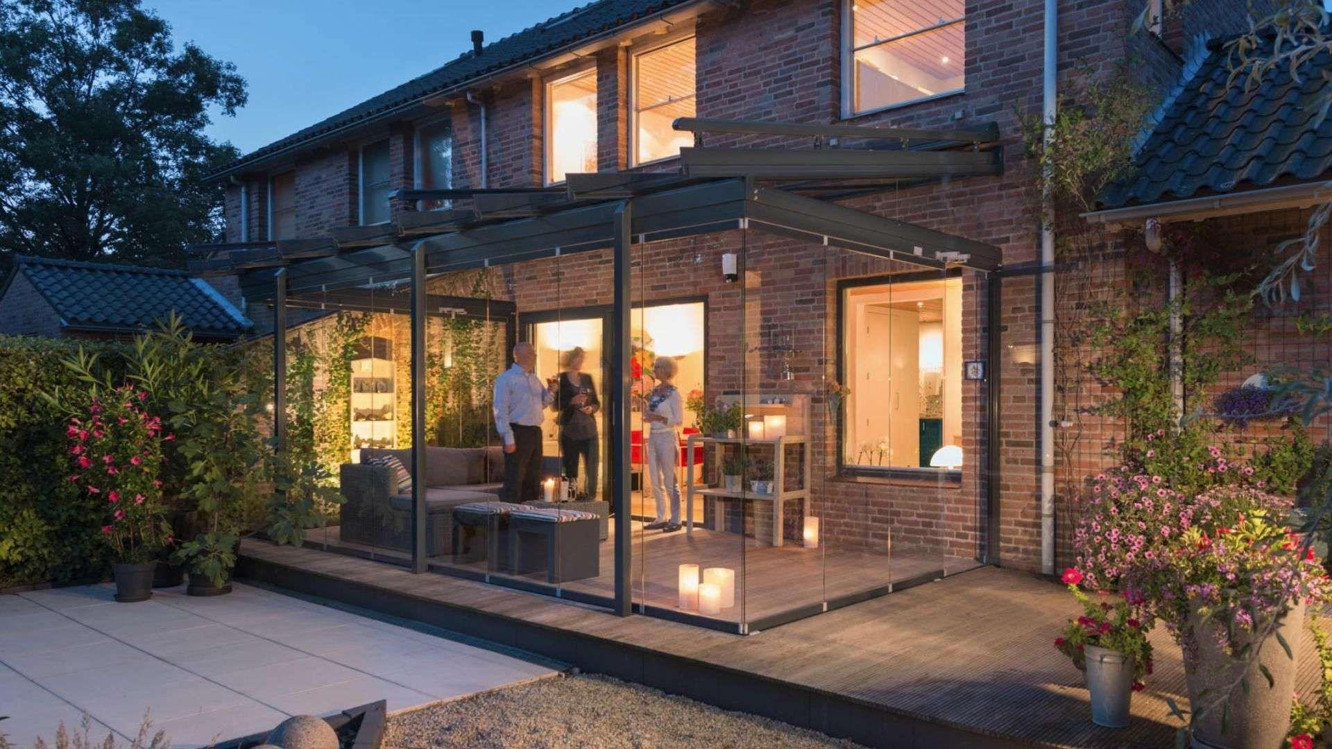 Solarlux SDL Atrium plus Terrassendach an einen Haus mit rotem Klinker bei Dämmerung. Unter dem Terrassendach stehen drei Personen.