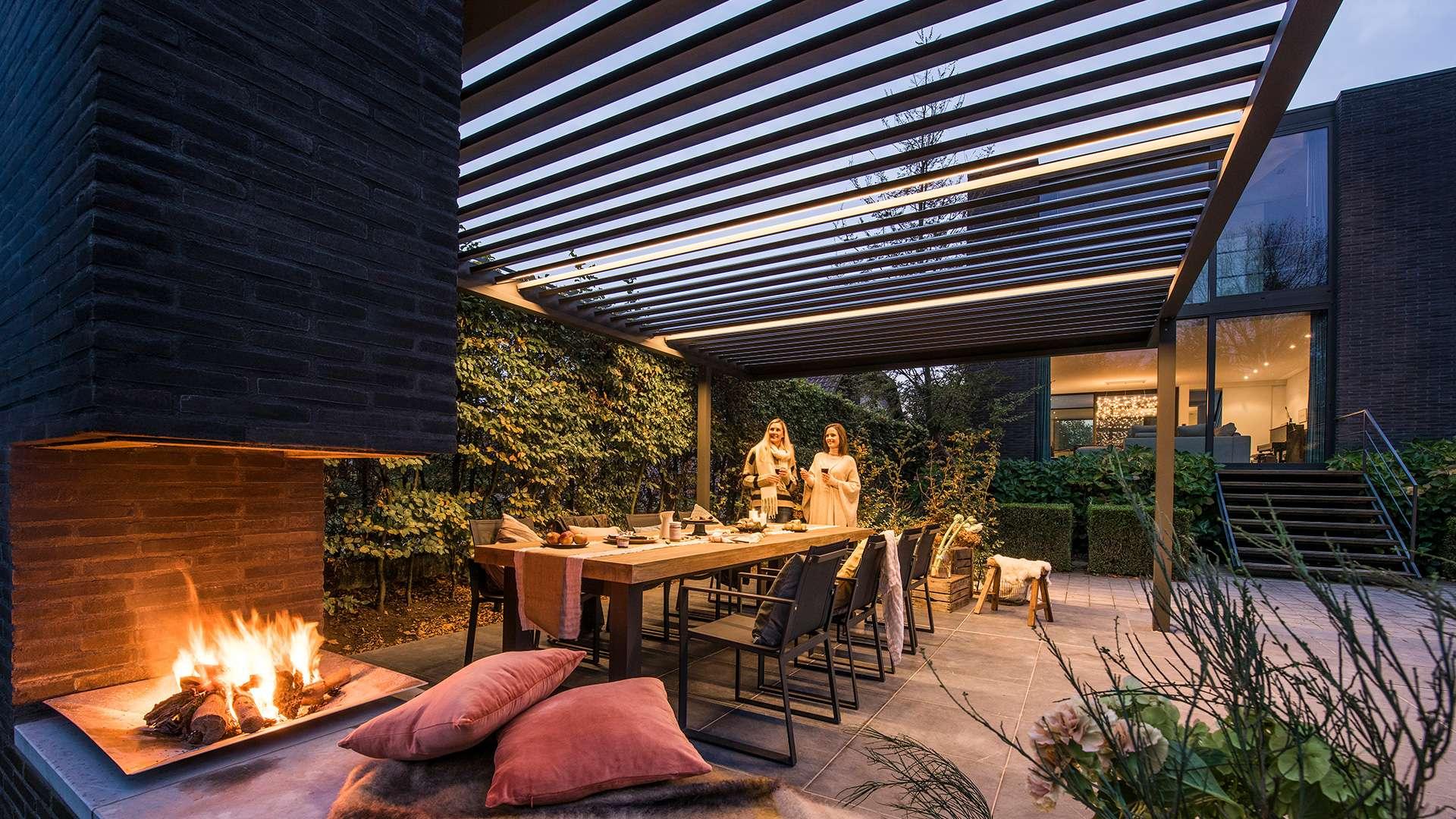 Lamellendach über einem Esstisch und einem Kamin auf einer Terrasse