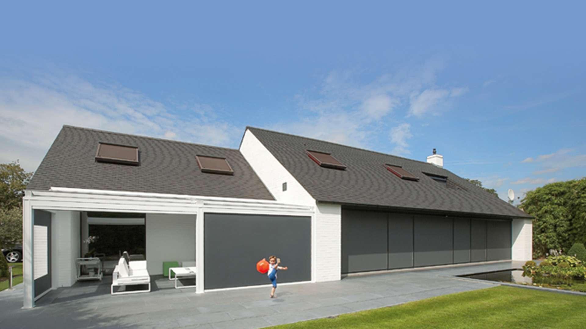 Windfester Sonnenschutz an einem Terrassendach an einem Wohnhaus