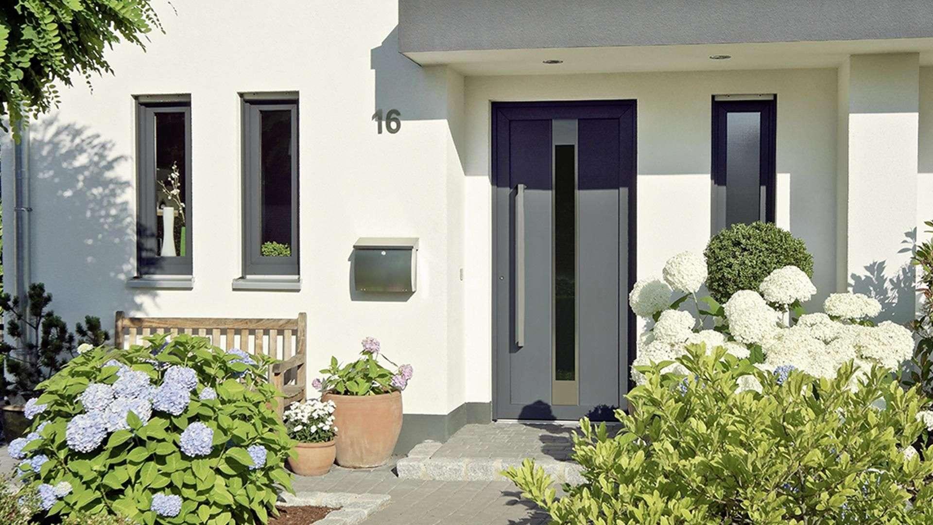 graue Haustür in hellgelber Fassade