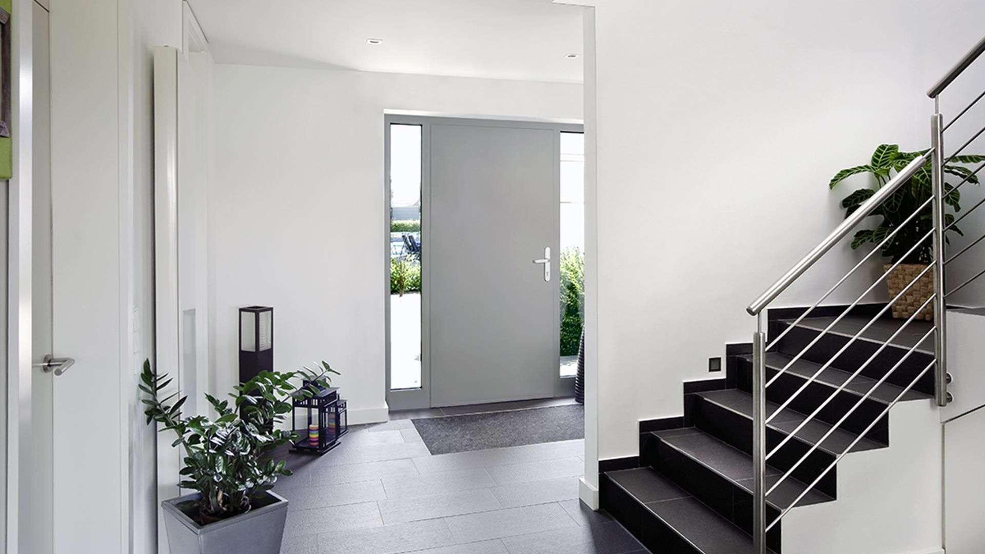 Eingangsbereich eines Hauses mit hellgrauer Haustür und Treppe in die erste Etage