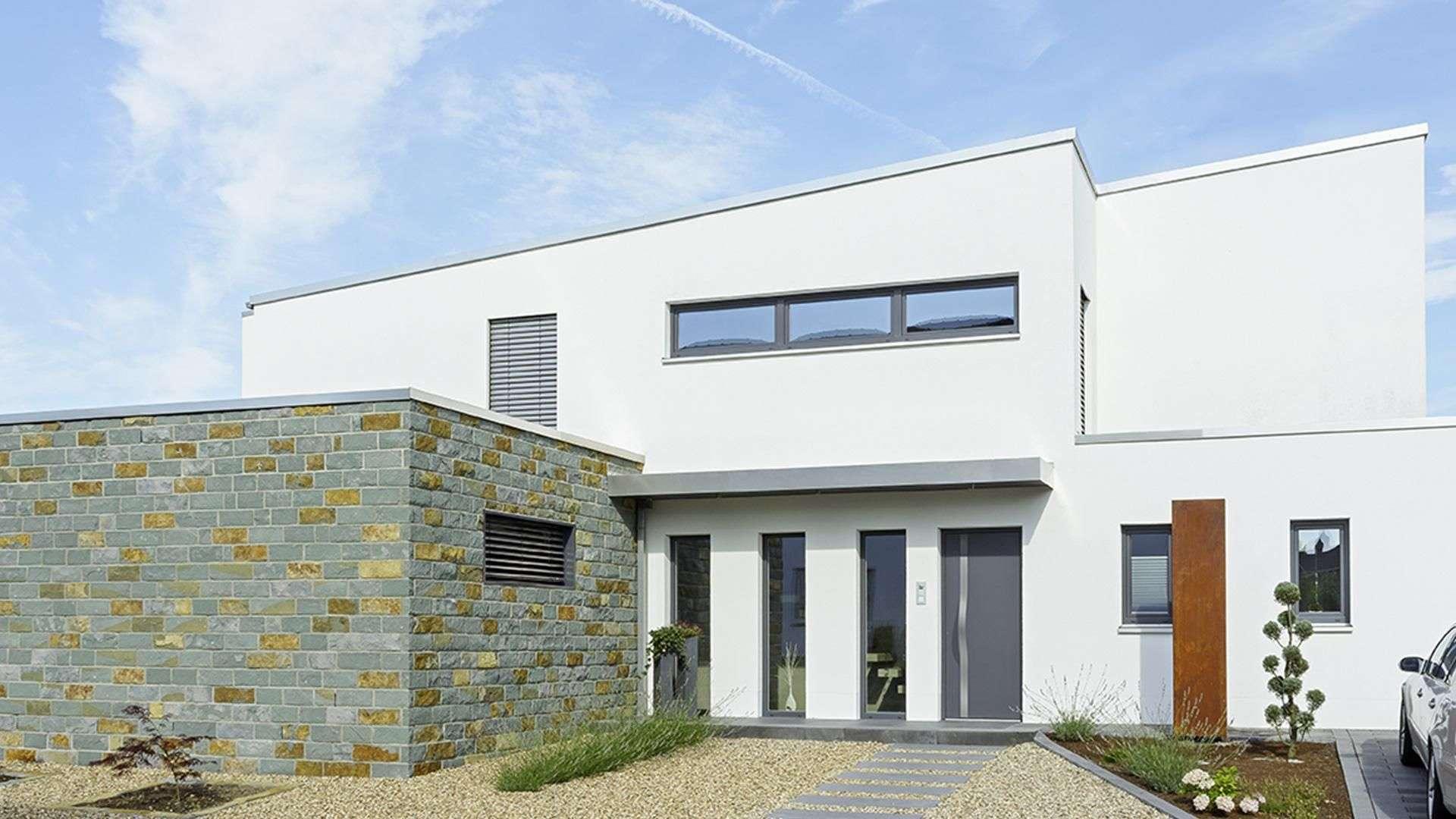 modernes weißes Pultdachhaus mit grauer Haustür und vielen Fenstern