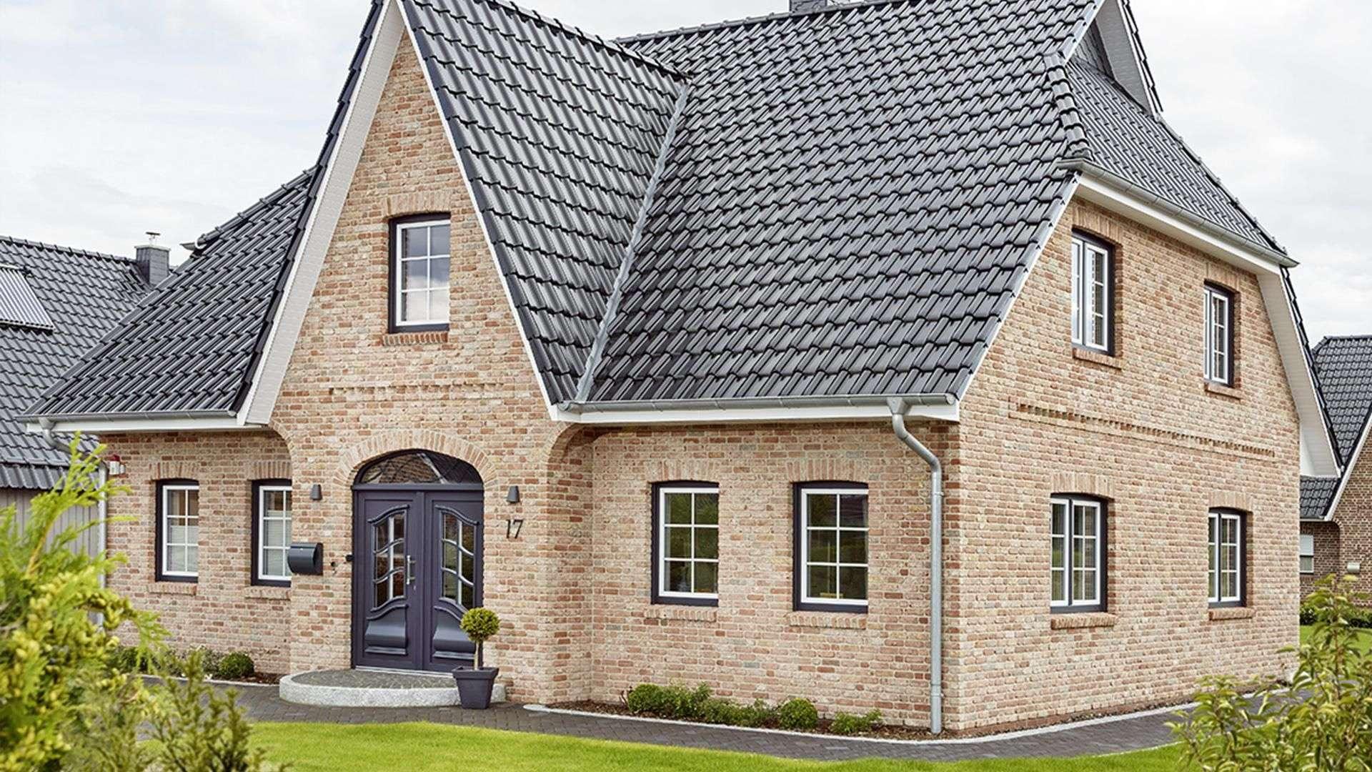 großes Wohnhaus mit dunkler Rundbogenhaustür und vielen Fenstern