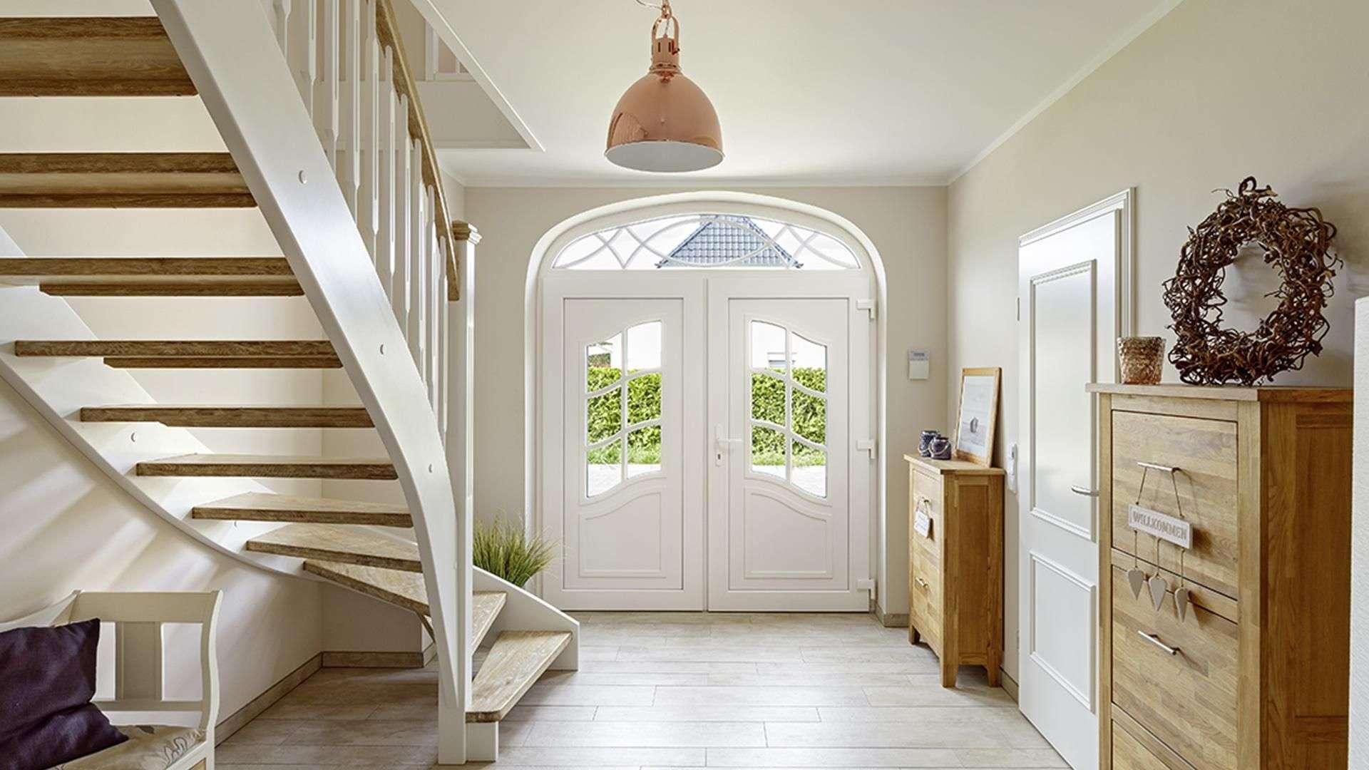 Eingangsbereich eines Hauses mit weißer Rundbogenhaustür und Holztreppe in die erste Etage
