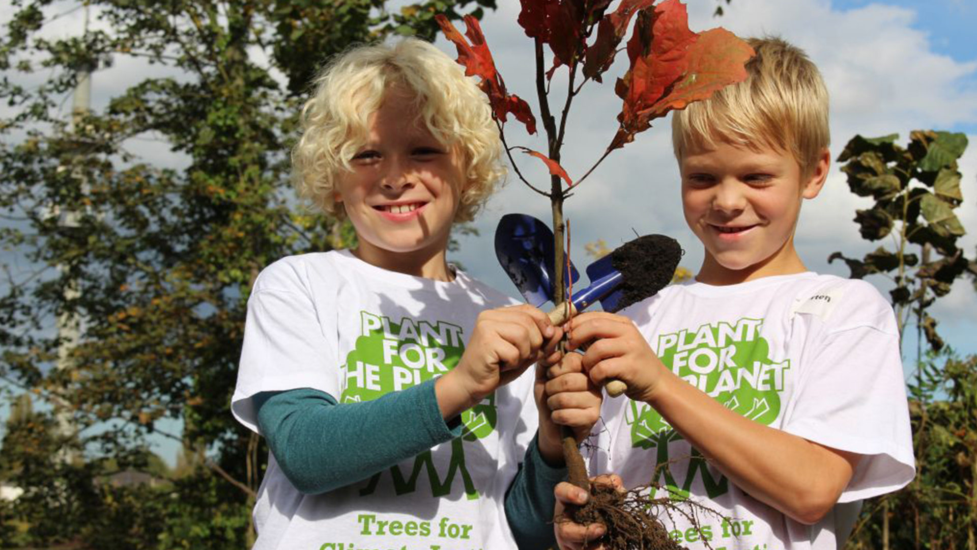 zwei Kinder halten einen kleinen Baum