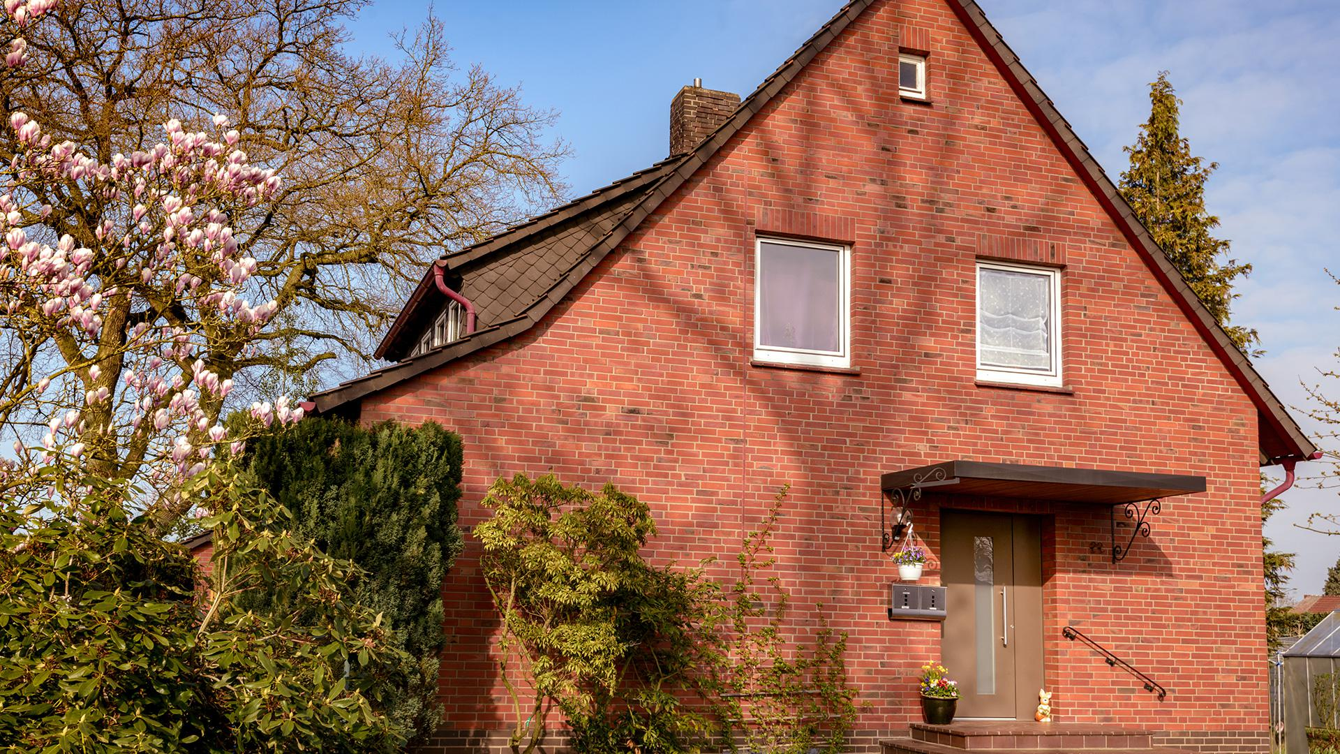 rotes Klinkerhaus mit brauner Haustür mit Vordach