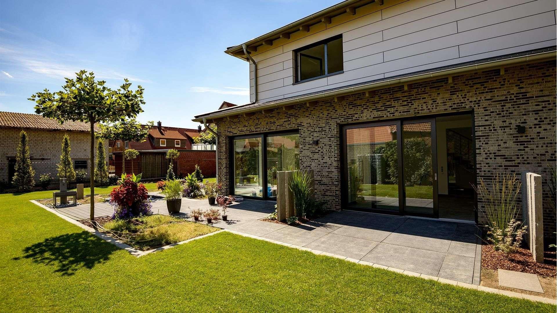 großes Wohnhaus mit bodentiefen Fenstern und großer Terrasse