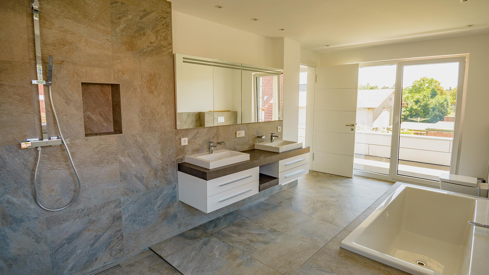 modernes Badezimmer mit bodentiefen Fenstern mit Blick in den Garten
