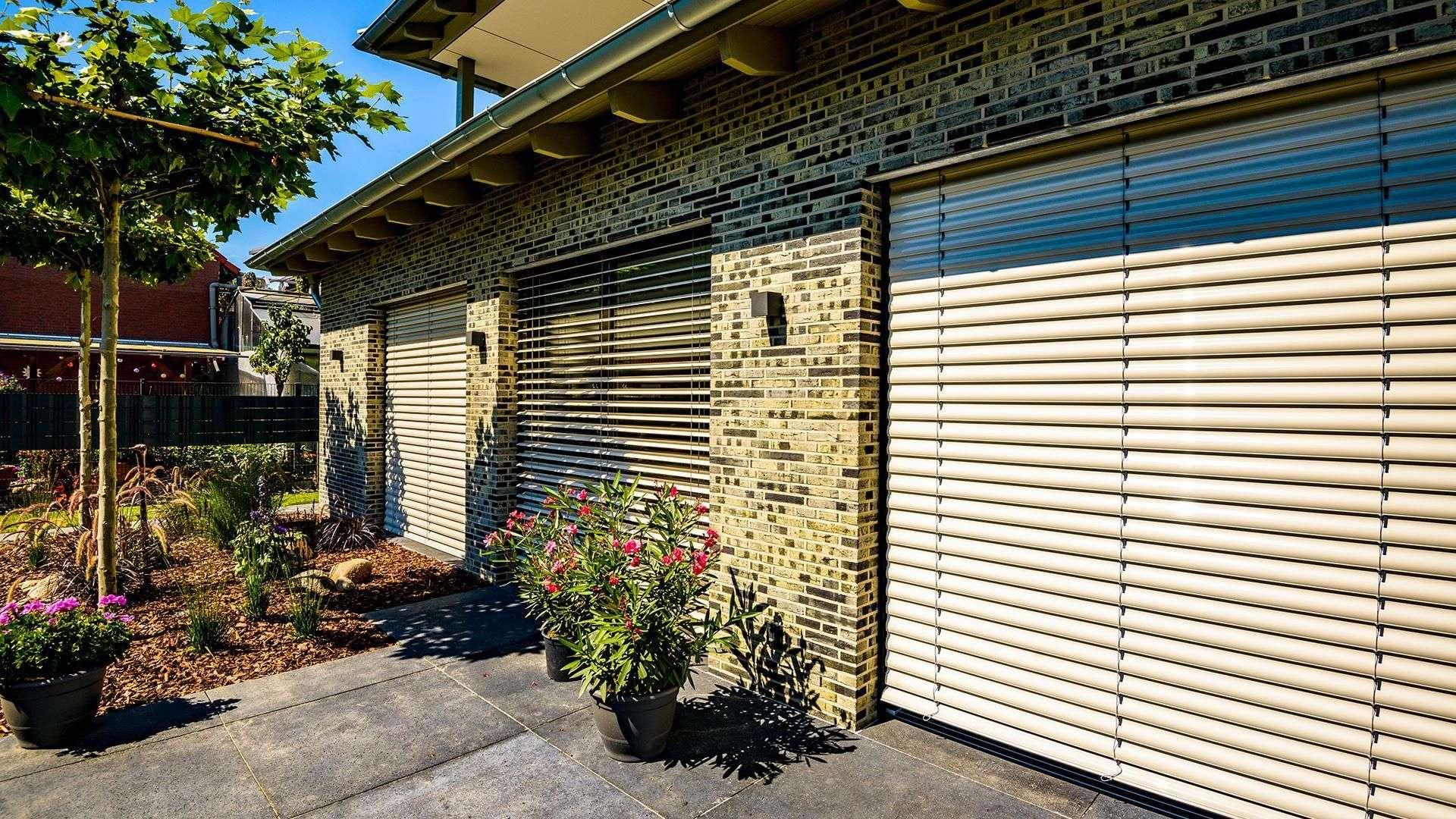 Wohnhaus mit Sonnenschutz-Rollos vor den bodentiefen Fenstern