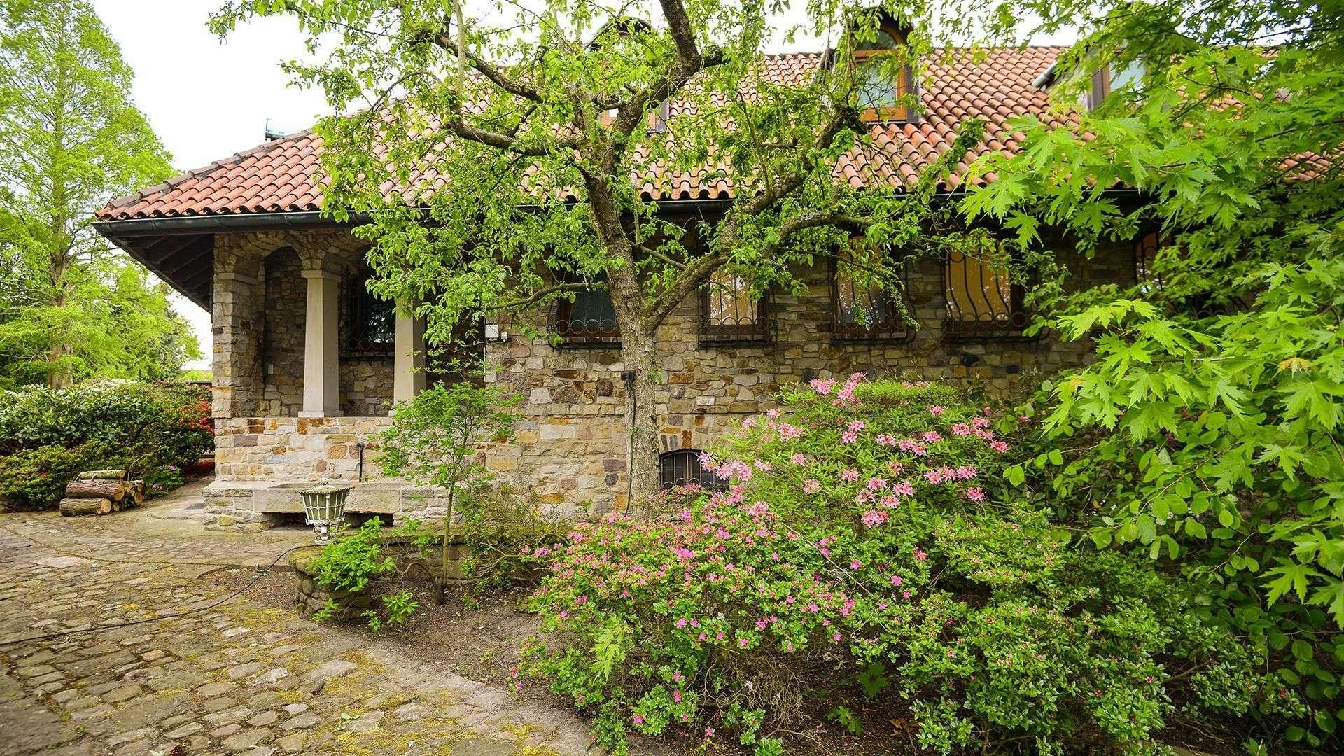 Steinhaus versteckt hinter Bäumen