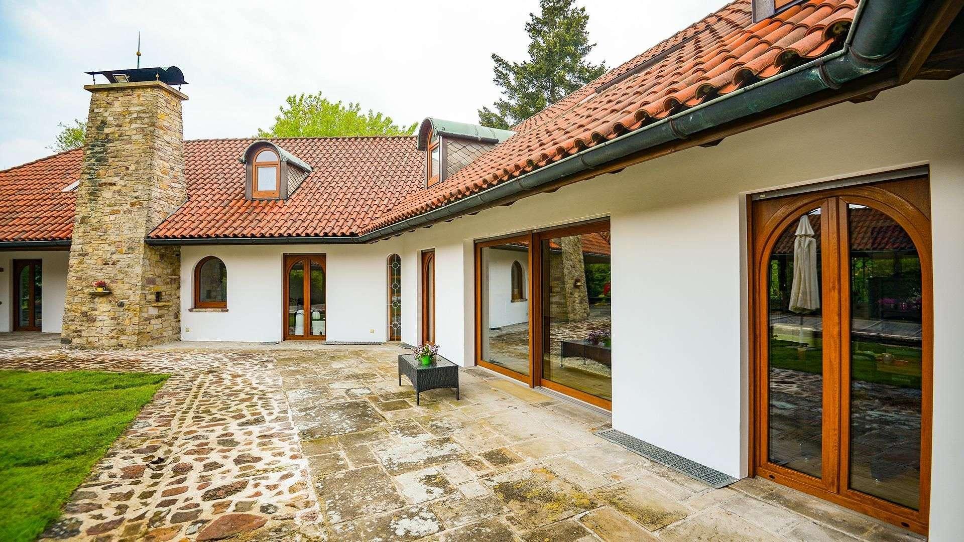 Innenhof einer Wohnanlage mit Holzfenstern und Steinterrasse