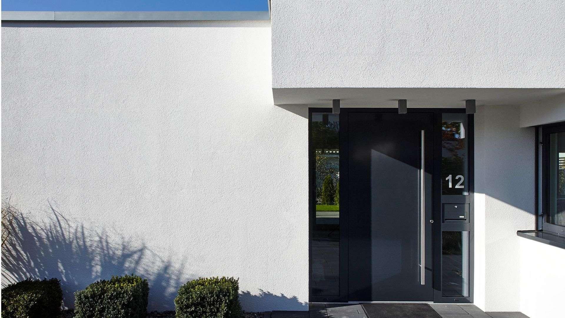 graue Haustür mit Glaselementen rechts und links in weißer Fassade
