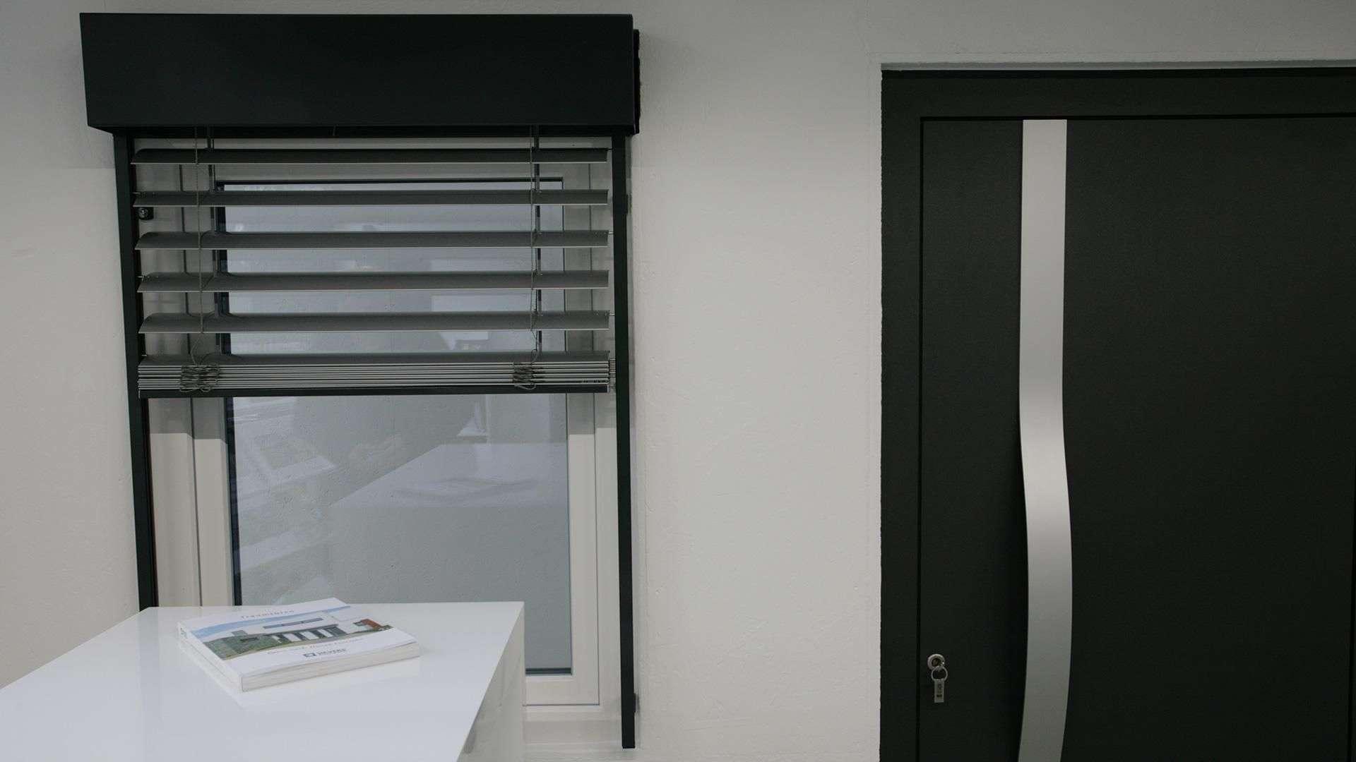Fenster mit Rollo neben einer Haustür in der Ausstellung von Sievers in Haßbergen