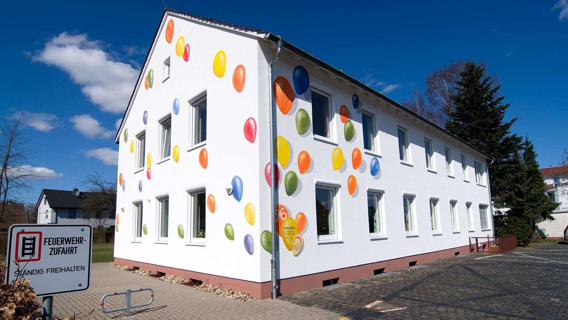 weißes großes Haus mit vielen Fensten und Luftballons, die an die Fassade gemalt sind