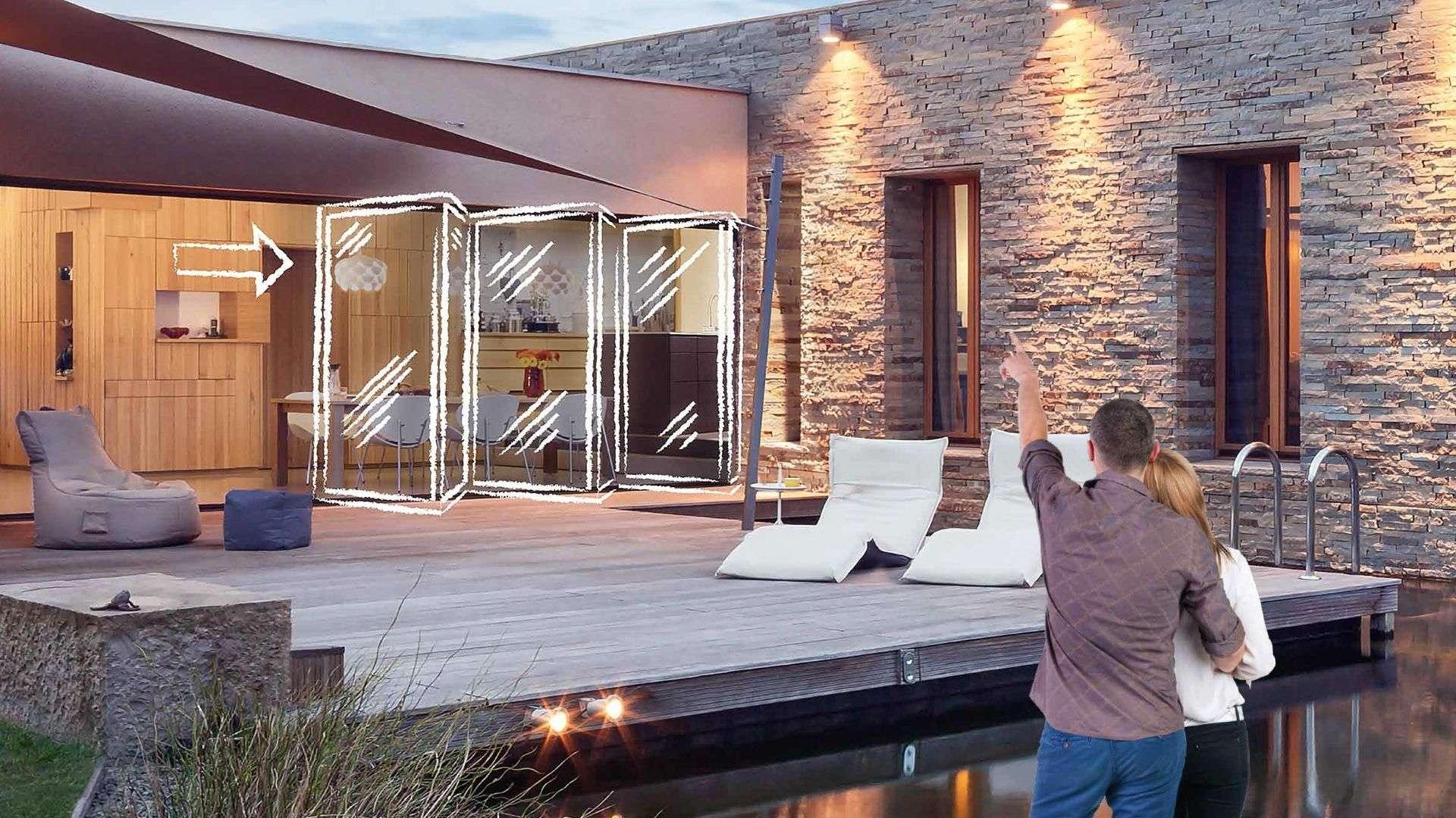 Terrasse auf der in weiße eine Glas-Faltwand skizziert ist. Im Vordergrund ein Pärchen, was auf dieses Bauvorhaben zeigt.