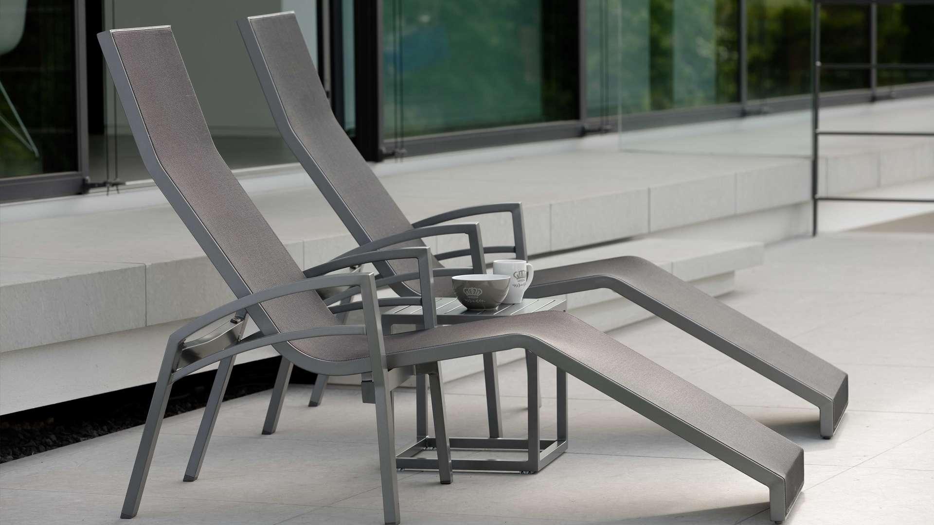 zwei Liegestühle auf einer Terrasse