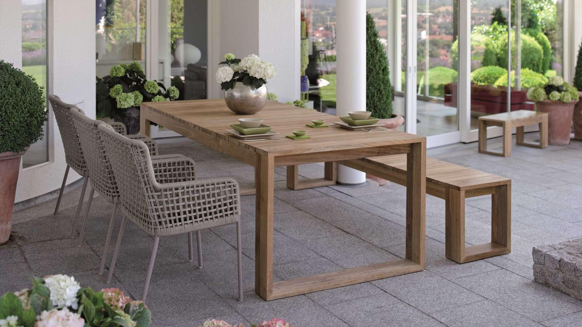 Esstisch mit Bank und Stühlen auf einer Terrasse