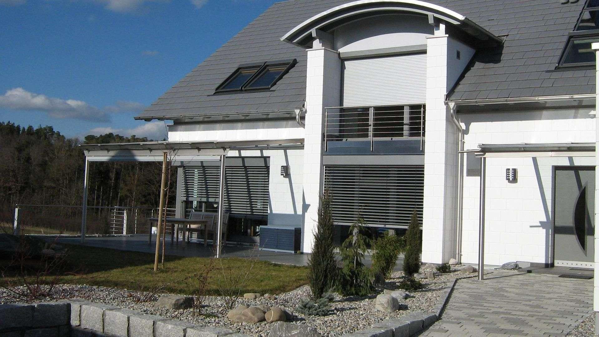 weißes Wohnhaus mit grauen Außenjalousien