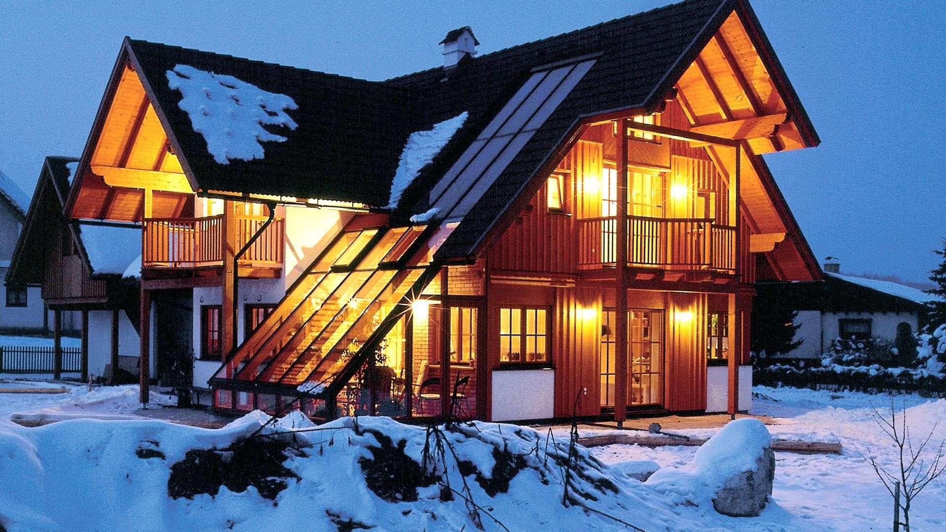 eingeschneites großes Haus bei Dämmerung, welches drinnen start beleuchtet ist
