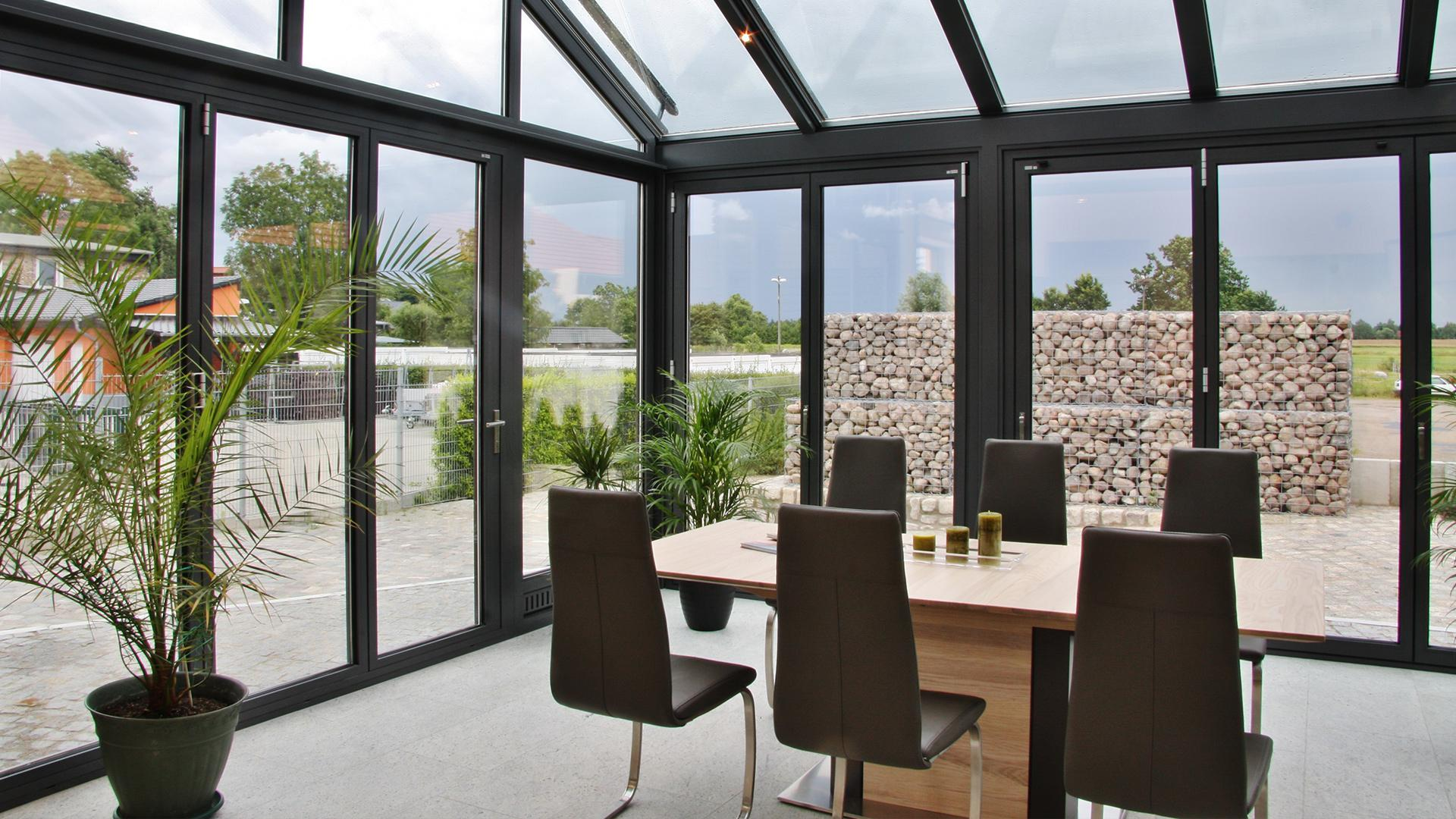 grauer Wintergarten mit Esstisch mit Blick in einen modernen Garten