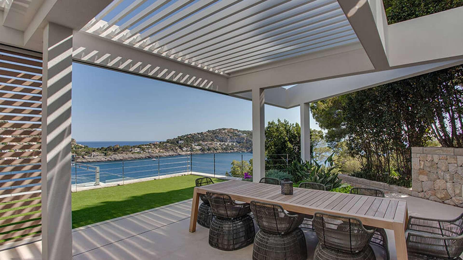 Innenansicht eines Aero Lamellendachs mit Esstisch und Blick auf einen Fluss