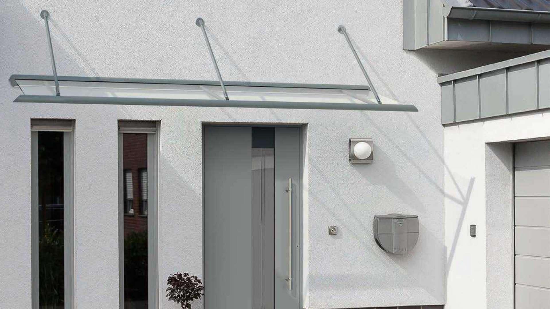 hellgraue Haustür mit zwei schmalen Fenstern links daneben in weißer Fassade. Alles wird von einem gläsernen Vordach überdacht.