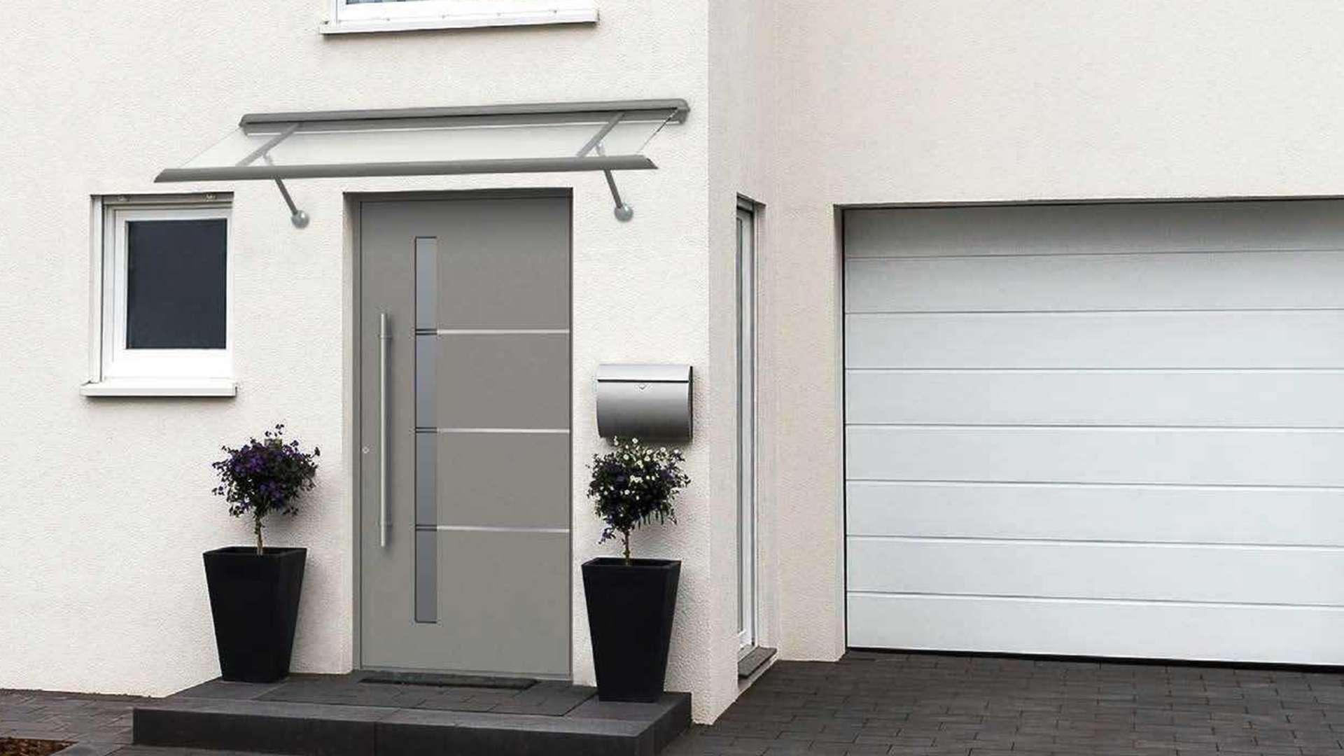 hellgraue Haustür in weißer Fassade mit Vordach aus Glas