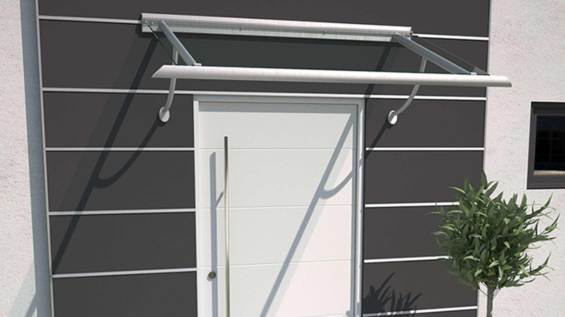 weiße Haustür in dunkler Fassade mit Vordach aus Glas